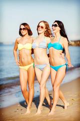 girls in bikini walking on the beach
