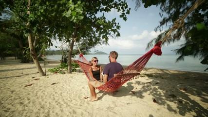 Couple using digital tablet on hammock