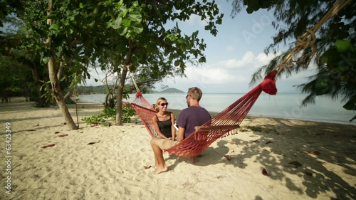 Couple using digital tablet on hammock