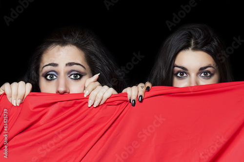 Girls hiding behind red cloth