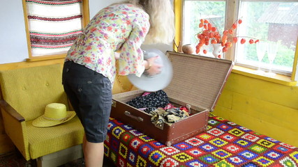 Blond woman girl pack her clothes into retro travel suitcase