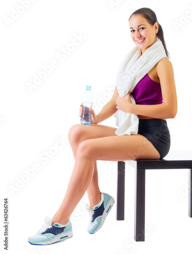 Young sporty girl with water bottle sit on bench