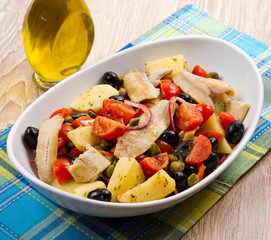 insalata di aringhe, patate, pomodori e olive