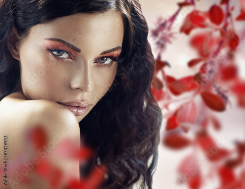 Sensual brunette lady over the petals background