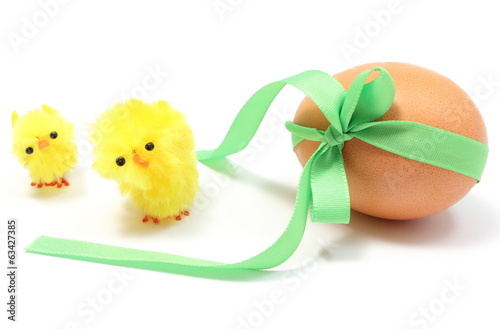 Easter chickens and egg with green ribbon. White background