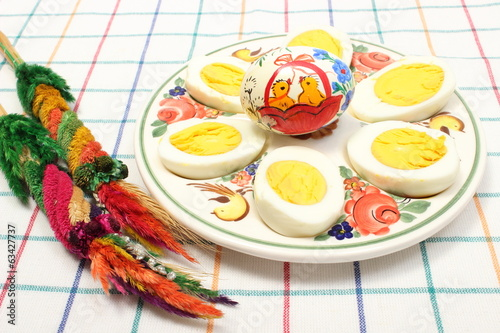 Easter palm, halves of eggs and painted egg on colorful plate