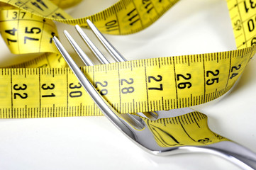 fork wrapped in measure tape in diet overweight concept