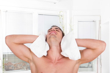 handsome guy drying hair with white towel
