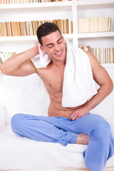handsome guy on sofa wearing pajamas and towel around neck