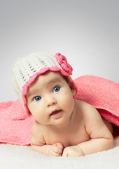 Funny little newborn baby wearing a hat with flower