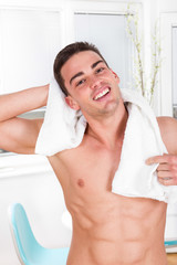handsome smiling man holding towel around his neck