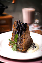 Piece of dark chocolate cake with chocolate frosting, walnuts an