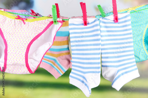 Baby clothes hanging on clothesline, on bright background
