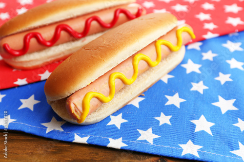 Tasty hot dogs on napkin with stars