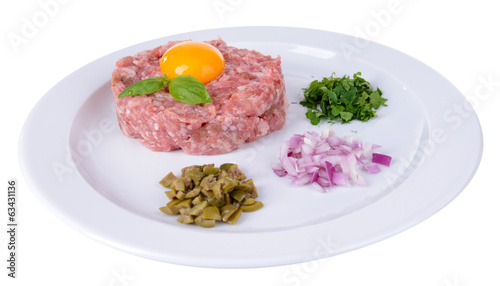 Delicious steak tartare with yolk on plate isolated on white