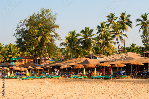 Palm trees and reed huts on a beach at sunset