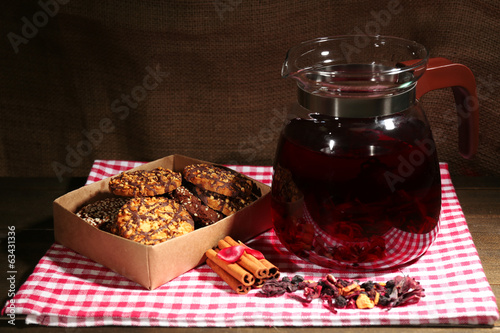 Jar of herbal tea and cookies on wooden table