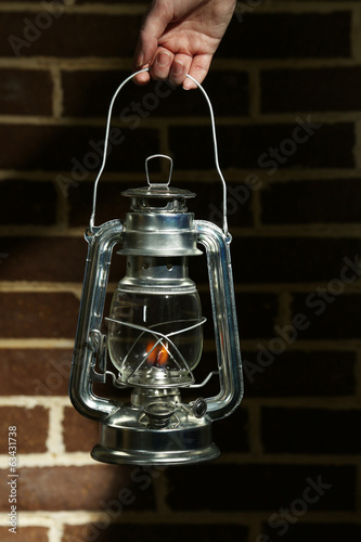 Hand holding kerosene lamp on brick wall background