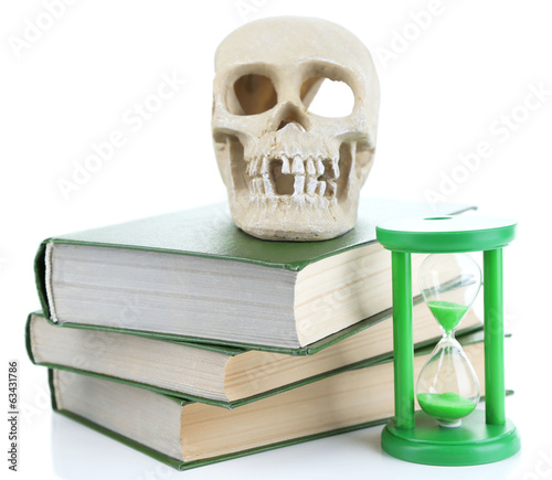 Hourglass and skull on old book isolated on white