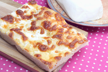 Focaccia with cheese on pink tablecloth