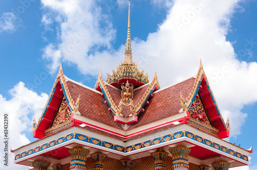 Top of traditional Thai style church with blue sky