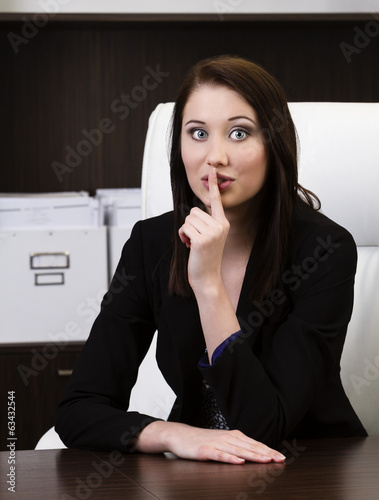 Young businesswoman showing quiet sign