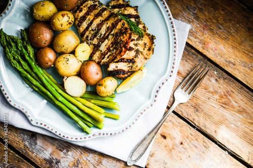 Grilled chicken with potatoes and asparagus on wooden background