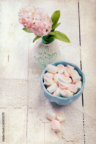 Pastel colored marshmallows and hyacinth flowers, on wooden desk