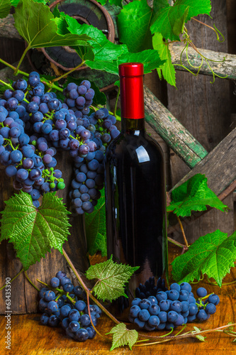 A bottle of red wine on the background of  grapes