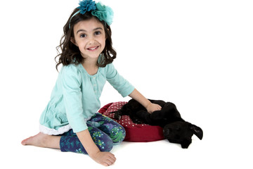 beautiful young girl playing with black labrador puppy