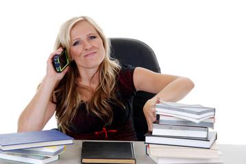 female model talking on her cellphone ignoring homework