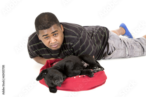 African American man laying by his labrador puppy