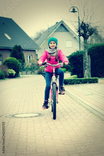 Cute smiling little girl with bicycle on road.Retro foto