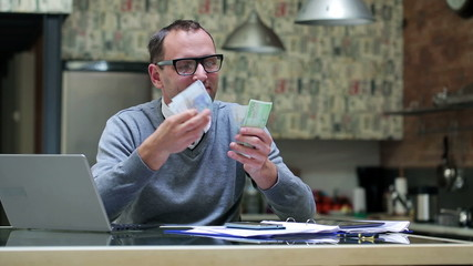 Satisfied man counting cash at home.