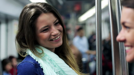 Happy women talking and smiling in subway, steadycam, shot.