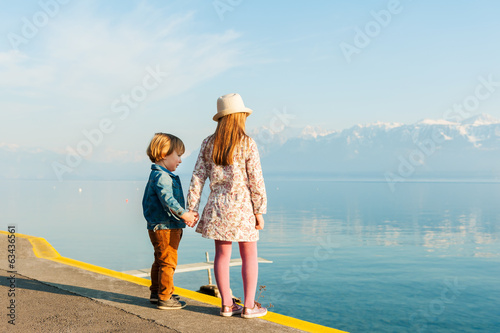 Adorable children resting next to lake on a nice sunny day