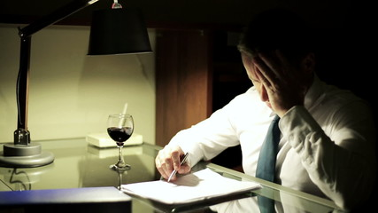 Businessman have headache at night work by the table.