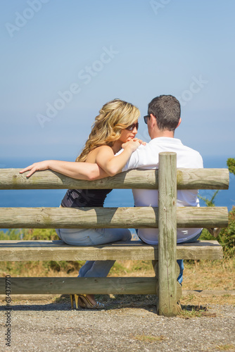 Back view of love couple sitting outdoors on bench