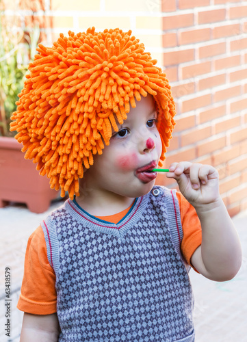 Clown child eating lollipop in a party