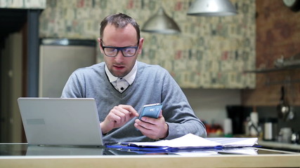 Businessman working on laptop and cellphone at home