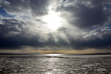 Sun through the stormy clouds at the frozen sea