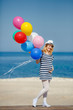 Pregnant woman in sunglasses and a white hat with balloons