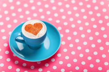 Cup of сoffee with shape heart on a table.