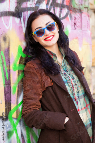 Teen girl near graffiti wall.