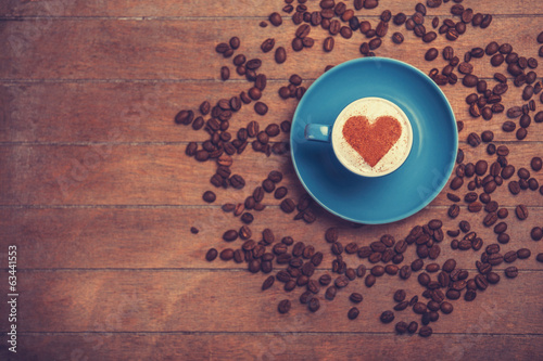 Cup of сoffee with shape heart on a wooden table.