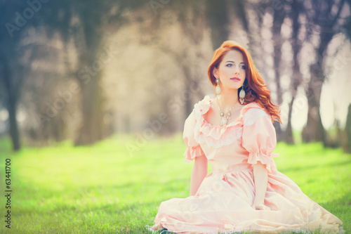 Beautiful women in dress sitting on a spring grass.