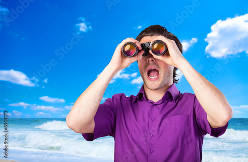 Handsome man with binocular near sea.