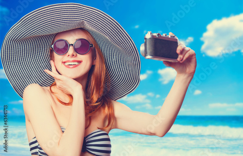 Beautiful redhead woman making selfie on a beach.