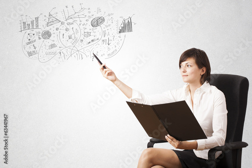 Pretty girl sketching graphs and diagrams on wall