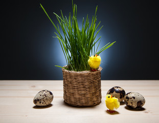 Easter still life with eggs, chickens, grass in a basket.